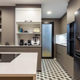 Diseño de cocina en U, actual, de tamaño medio, con armarios con paneles lisos, puertas de armario grises, salpicadero blanco, electrodomésticos negros, península, suelo multicolor y encimeras blancas
