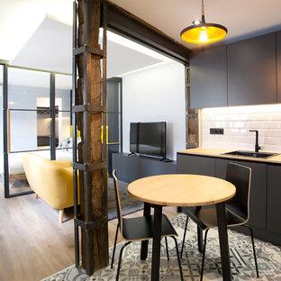 Idee per una cucina moderna di medie dimensioni con lavello integrato, ante con riquadro incassato, top in legno, paraspruzzi nero, paraspruzzi con piastrelle di metallo, pavimento in gres porcellanato, pavimento grigio e top marrone