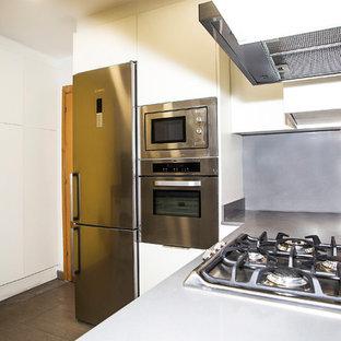 バルセロナの中くらいのコンテンポラリースタイルのおしゃれなコの字型キッチン (シングルシンク、白いキャビネット、グレーのキッチンパネル、シルバーの調理設備、無垢フローリング、アイランドなし) の写真