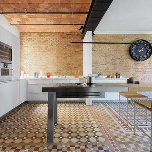 Modelo de cocina en L, mediterránea, con armarios con paneles lisos, puertas de armario blancas, encimera de acero inoxidable, una isla y suelo multicolor