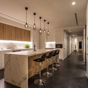 Imagen de cocina lineal, actual, con armarios con paneles lisos, puertas de armario de madera oscura, encimera de cuarzo compacto, salpicadero blanco, una isla, encimeras blancas y suelo negro