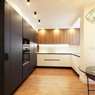 Diseño de cocina comedor en U, contemporánea, grande, con armarios con paneles lisos, puertas de armario negras, salpicadero blanco, suelo laminado y electrodomésticos negros
