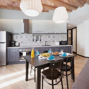 Ejemplo de cocina lineal, urbana, abierta, con fregadero encastrado, armarios con paneles lisos, puertas de armario marrones, salpicadero multicolor, electrodomésticos de acero inoxidable, suelo de madera clara y encimeras blancas