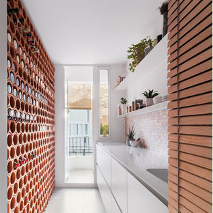 Inspiration for a mid-sized scandinavian single-wall open plan kitchen in Valencia with a single-bowl sink, louvered cabinets, beige cabinets, stainless steel benchtops, multi-coloured splashback, cement tile splashback, panelled appliances, ceramic floors, no island, grey floor and white benchtop.