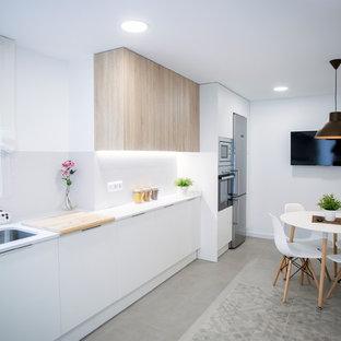 Foto de cocina comedor lineal, contemporánea, grande, sin isla, con fregadero de un seno, armarios con paneles lisos, puertas de armario blancas, salpicadero blanco, electrodomésticos de acero inoxidable, encimeras blancas y suelo gris