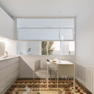 Design ideas for a large transitional l-shaped eat-in kitchen in Valencia with an undermount sink, flat-panel cabinets, light wood cabinets, quartz benchtops, beige splashback, limestone splashback, white appliances, cement tiles, no island, multi-coloured floor and beige benchtop.