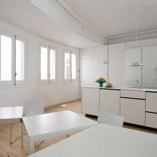 Imagen de cocina de galera, actual, abierta, con fregadero integrado, armarios con paneles lisos, puertas de armario blancas, electrodomésticos con paneles, suelo de madera clara, una isla, suelo beige y encimeras blancas