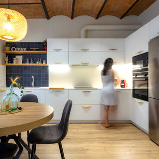 Imagen de cocina en L, costera, de tamaño medio, abierta, sin isla, con fregadero de un seno, puertas de armario blancas, electrodomésticos de acero inoxidable, suelo de madera en tonos medios y suelo marrón