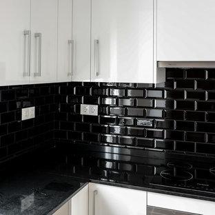 Modern inredning av ett mellanstort kök, med en nedsänkt diskho, släta luckor, vita skåp, granitbänkskiva, svart stänkskydd, stänkskydd i keramik, rostfria vitvaror och laminatgolv