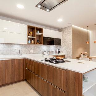 Modelo de cocina comedor en U, actual, con fregadero encastrado, armarios con paneles lisos, puertas de armario de madera oscura, salpicadero verde, península, suelo beige y encimeras blancas