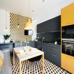 Foto de cocina comedor en L, actual, con armarios con paneles lisos, puertas de armario amarillas, salpicadero multicolor, electrodomésticos negros, suelo multicolor y encimeras grises
