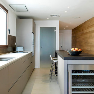Modelo de cocina lineal, contemporánea, con fregadero de doble seno, armarios con paneles lisos, puertas de armario grises, salpicadero metalizado, una isla, suelo gris y encimeras negras