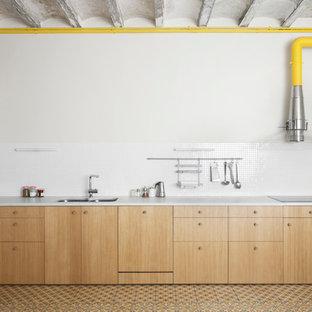 Modelo de cocina lineal, urbana, sin isla, con fregadero de doble seno, armarios con paneles lisos, puertas de armario de madera clara, salpicadero blanco, suelo multicolor y encimeras blancas