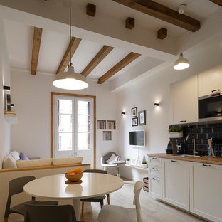 Mid-sized scandinavian single-wall eat-in kitchen in Barcelona with recessed-panel cabinets, white cabinets, wood benchtops, black splashback, subway tile splashback, no island, a single-bowl sink, stainless steel appliances, light hardwood floors and beige floor.