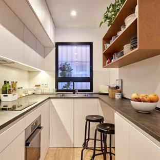 Diseño de cocina en U, actual, pequeña, cerrada, con fregadero encastrado, armarios con paneles lisos, puertas de armario blancas, salpicadero blanco, electrodomésticos de acero inoxidable, suelo de madera clara, suelo beige y encimeras grises