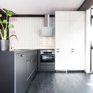 Foto de cocina en L, contemporánea, de tamaño medio, con armarios con paneles lisos, puertas de armario negras, salpicadero blanco, electrodomésticos de acero inoxidable, península y suelo negro