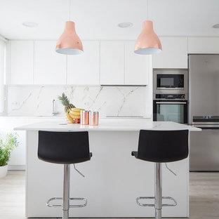 Modelo de cocina lineal, contemporánea, de tamaño medio, con armarios con paneles lisos, puertas de armario blancas, encimera de mármol, salpicadero blanco, electrodomésticos de acero inoxidable, una isla y encimeras blancas