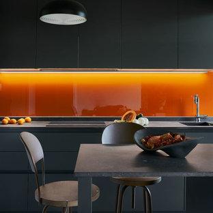 Imagen de cocina de galera, contemporánea, grande, con fregadero bajoencimera, armarios con paneles lisos, puertas de armario grises, salpicadero naranja, salpicadero de vidrio templado, electrodomésticos con paneles, una isla, suelo gris y encimeras grises