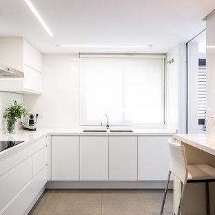 Imagen de cocina en L, actual, de tamaño medio, con fregadero bajoencimera, armarios con paneles lisos, puertas de armario blancas, salpicadero blanco, electrodomésticos de acero inoxidable, suelo de baldosas de porcelana, suelo gris y encimeras blancas