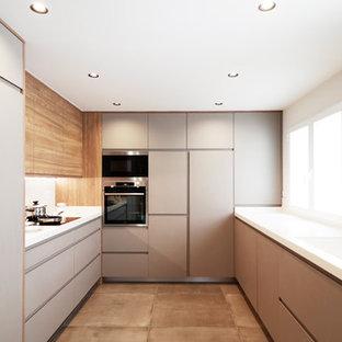 Modelo de cocina en U, moderna, grande, cerrada, sin isla, con fregadero integrado, armarios con paneles lisos, puertas de armario grises, salpicadero blanco, encimeras blancas, electrodomésticos con paneles, suelo de cemento y suelo beige