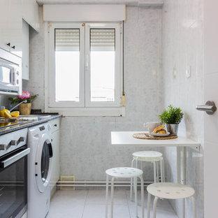 Modelo de cocina lineal, contemporánea, sin isla, con armarios con paneles lisos, puertas de armario blancas, electrodomésticos de acero inoxidable, suelo blanco y encimeras negras