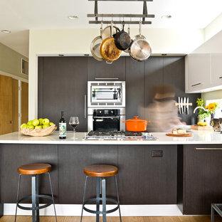 Ejemplo de cocina en U, contemporánea, de tamaño medio, con armarios con paneles lisos, puertas de armario negras, electrodomésticos de acero inoxidable, península, suelo de madera en tonos medios, suelo marrón, encimeras blancas y salpicadero blanco