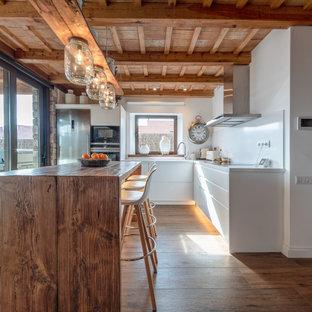 Свежая идея для дизайна: угловая кухня в стиле кантри с плоскими фасадами, белыми фасадами, техникой из нержавеющей стали, паркетным полом среднего тона, островом, коричневым полом, белой столешницей, балками на потолке и деревянным потолком - отличное фото интерьера