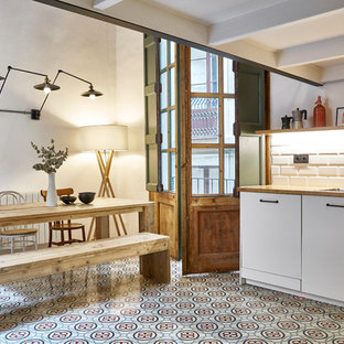 This is an example of a mid-sized modern l-shaped eat-in kitchen in Barcelona with a drop-in sink, flat-panel cabinets, white cabinets, wood benchtops, white splashback, ceramic splashback, stainless steel appliances, terra-cotta floors, no island and multi-coloured floor.