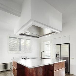 Diseño de cocina lineal, clásica renovada, grande, abierta, con fregadero integrado, armarios con paneles lisos, puertas de armario de madera en tonos medios, electrodomésticos de acero inoxidable, suelo de baldosas de cerámica y una isla
