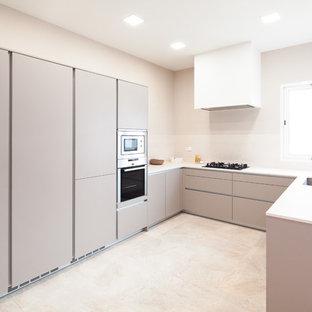 Foto de cocina en U, contemporánea, sin isla, con armarios con paneles lisos, puertas de armario grises, fregadero bajoencimera, suelo beige y encimeras blancas
