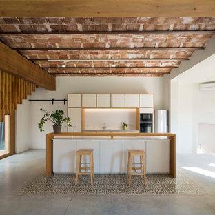 Modelo de cocina lineal, mediterránea, grande, abierta, con armarios con paneles lisos, puertas de armario blancas, encimera de madera, salpicadero blanco, electrodomésticos de acero inoxidable, una isla, suelo de cemento y suelo gris