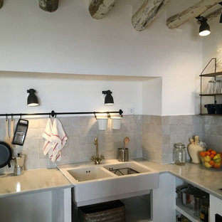 Small mediterranean open concept kitchen designs - Example of a small tuscan u-shaped cement tile floor and multicolored floor open concept kitchen design in Madrid with a double-bowl sink, open cabinets, marble countertops, black appliances, an island and white countertops