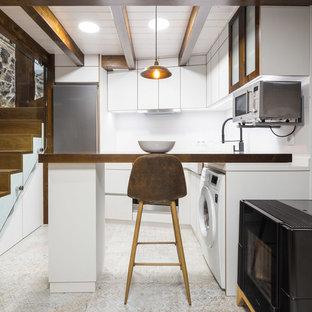 Modelo de cocina en L, urbana, cerrada, con armarios con paneles lisos, puertas de armario blancas, encimera de madera, salpicadero blanco, electrodomésticos de acero inoxidable, suelo de azulejos de cemento, península, suelo beige y encimeras marrones