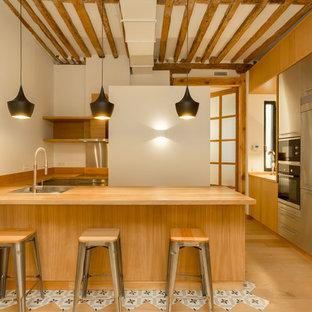 マドリードの中サイズの地中海スタイルのおしゃれなキッチン (フラットパネル扉のキャビネット、中間色木目調キャビネット、木材カウンター、白いキッチンパネル、ドロップインシンク、シルバーの調理設備の、淡色無垢フローリング、ベージュの床) の写真