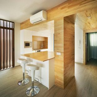 Idéer för ett mellanstort modernt orange linjärt kök med öppen planlösning, med släta luckor, vita skåp, mellanmörkt trägolv och en halv köksö