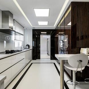 Ejemplo de cocina en L, contemporánea, de tamaño medio, cerrada, con fregadero bajoencimera, armarios con paneles lisos, puertas de armario blancas, salpicadero blanco y península