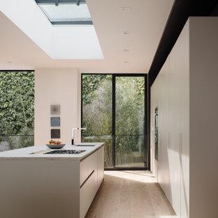 Diseño de cocina de galera, minimalista, con fregadero bajoencimera, armarios con paneles lisos, puertas de armario blancas, electrodomésticos de acero inoxidable, suelo de madera clara, una isla, suelo beige y encimeras blancas