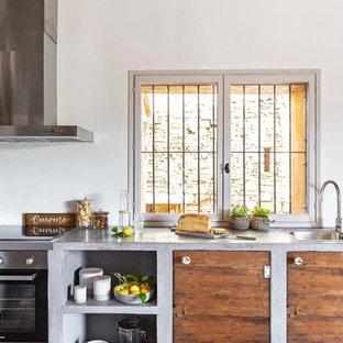 Foto de cocina lineal, mediterránea, grande, con fregadero encastrado, armarios con paneles lisos, puertas de armario de madera oscura, encimera de cemento, salpicadero blanco, suelo marrón y encimeras grises