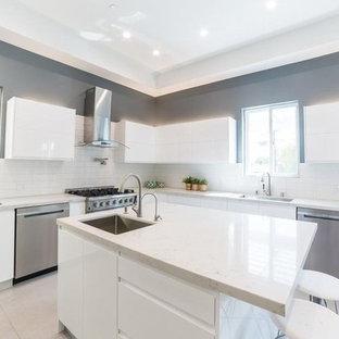 Идея дизайна: огромная угловая кухня-гостиная в стиле модернизм с одинарной раковиной, плоскими фасадами, белыми фасадами, столешницей из кварцевого композита, белым фартуком, фартуком из удлиненной плитки, техникой из нержавеющей стали, полом из керамогранита, островом, бежевым полом и белой столешницей