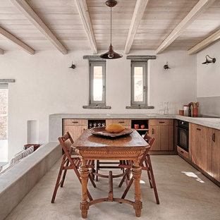 Inspiration for a mid-sized mediterranean l-shaped eat-in kitchen in Barcelona with an undermount sink, flat-panel cabinets, medium wood cabinets, limestone benchtops, grey splashback, black appliances, no island, concrete floors, grey floor and grey benchtop.