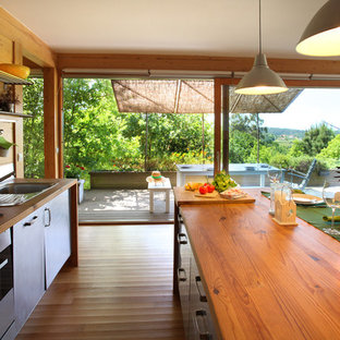 This is an example of a mid-sized tropical single-wall eat-in kitchen in Other with a drop-in sink, flat-panel cabinets, stainless steel cabinets, wood benchtops, metallic splashback, metal splashback, stainless steel appliances, medium hardwood floors, with island and multi-coloured floor.