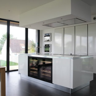 Inspiration for a mid-sized contemporary single-wall open plan kitchen in Other with an integrated sink, flat-panel cabinets, white cabinets, recycled glass benchtops, white splashback, window splashback, stainless steel appliances, slate floors, with island and black floor.