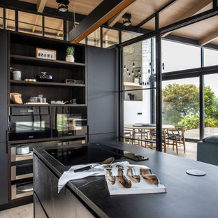 Photo of a mid-sized tropical l-shaped separate kitchen in Other with flat-panel cabinets, black cabinets, porcelain floors, with island, beige floor, black benchtop and wood.
