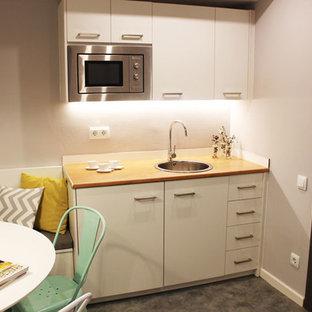 バルセロナの小さい北欧スタイルのおしゃれなキッチン (一体型シンク、フラットパネル扉のキャビネット、白いキャビネット、木材カウンター、グレーのキッチンパネル、シルバーの調理設備、クッションフロア、アイランドなし) の写真