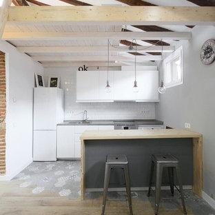 Imagen de cocina de galera, nórdica, de tamaño medio, abierta, con armarios con paneles lisos, puertas de armario blancas, salpicadero blanco, salpicadero de azulejos tipo metro, península y electrodomésticos blancos
