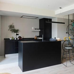 Imagen de cocina lineal, actual, de tamaño medio, abierta, con armarios con paneles lisos, puertas de armario negras, salpicadero beige, una isla y encimeras negras