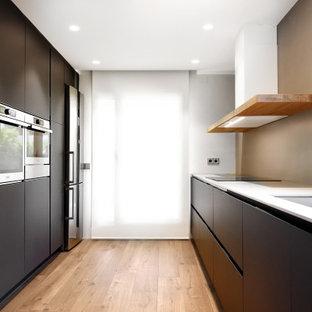 Ejemplo de cocina de galera, minimalista, con fregadero bajoencimera, armarios con paneles lisos, puertas de armario negras, electrodomésticos de acero inoxidable, suelo de madera clara y encimeras blancas