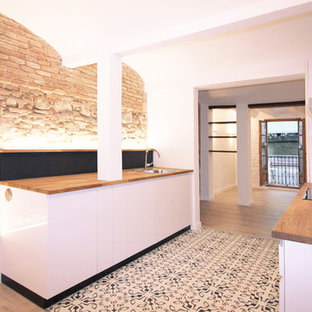 Photo of a mid-sized mediterranean single-wall open plan kitchen in Barcelona with an undermount sink, wood benchtops, black splashback, slate splashback, panelled appliances, cement tiles, multi-coloured floor, flat-panel cabinets, white cabinets, no island and brown benchtop.