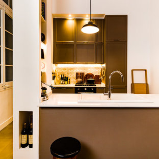 Mid-sized midcentury galley open plan kitchen in Barcelona with a drop-in sink, recessed-panel cabinets, beige cabinets, white splashback, black appliances and no island.