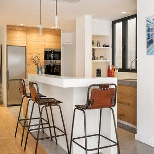 Diseño de cocina en L, contemporánea, con fregadero bajoencimera, armarios con paneles lisos, puertas de armario de madera oscura, salpicadero blanco, electrodomésticos de acero inoxidable, suelo de cemento, una isla, suelo gris y encimeras blancas
